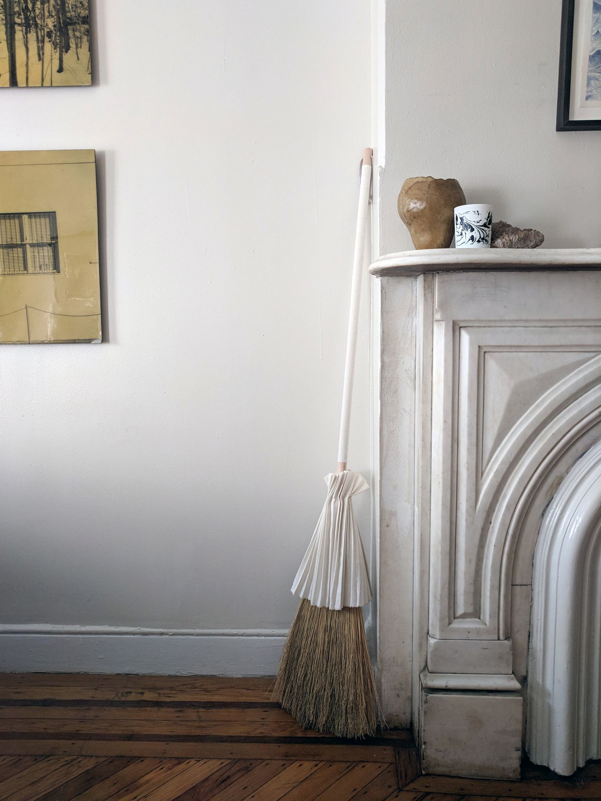 A broom with a skirt and sheath leans against a mantlepiece.