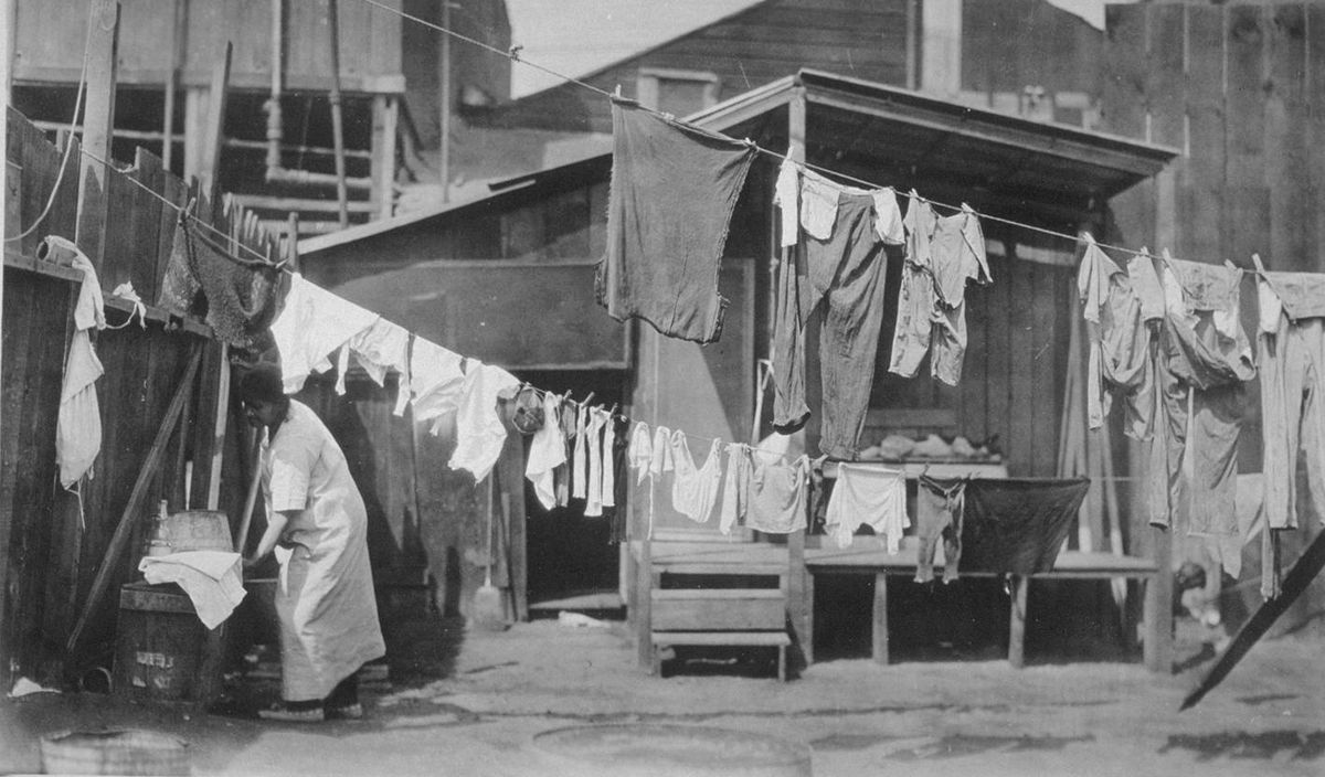 A wood shack on a dirt lot is festooned in clothes lines. Rags and clothing are draped on the lines, and a woman in a white dress washes clothes by hand.