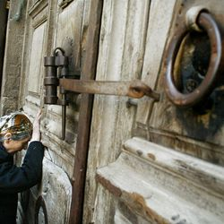 """**ADVANCE FOR FRIDAY MARCH 21**  **  FILE  ** A Christian pilgrim prays at the locked doors of the Church of the Holy Sepulchre in Jerusalem's Old City, in this  April 8, 2004 file photo. The doors are sealed shut during the Easter processions for different denominations. Christians traditionally believe the church is where Jesus was crucified and buried and people of all denominations mark the Easter Holiday in a week long celebration of the crucifixion and resurrection of Jesus Christ. On Easter Sunday, Christians will proclaim the message at the heart of their faith, """"He is risen,"""" and will affirm the hope that God will raise all the dead at the end of time. But this belief at the foundation of Christianity is deeply misunderstood, say scholars, who have been trying to clear up the confusion in several recent books. (AP Photo/Kevin Frayer, File)"""
