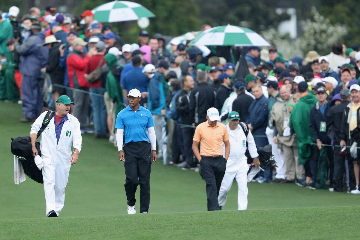 Tiger Woods of the United States and Ian Poulter of England walk with caddie Joe LaCava and caddie Terry Mundy on the first hole during the third round of the 2018 Masters Tournament at Augusta National Golf Club on April 7, 2018 in Augusta, Georgia.
