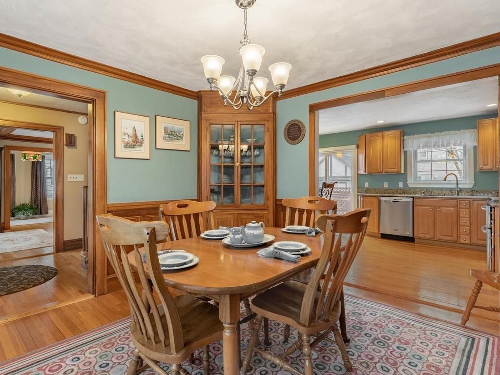A dining room with a table and chairs, and there's a built-in hutch in the corner.