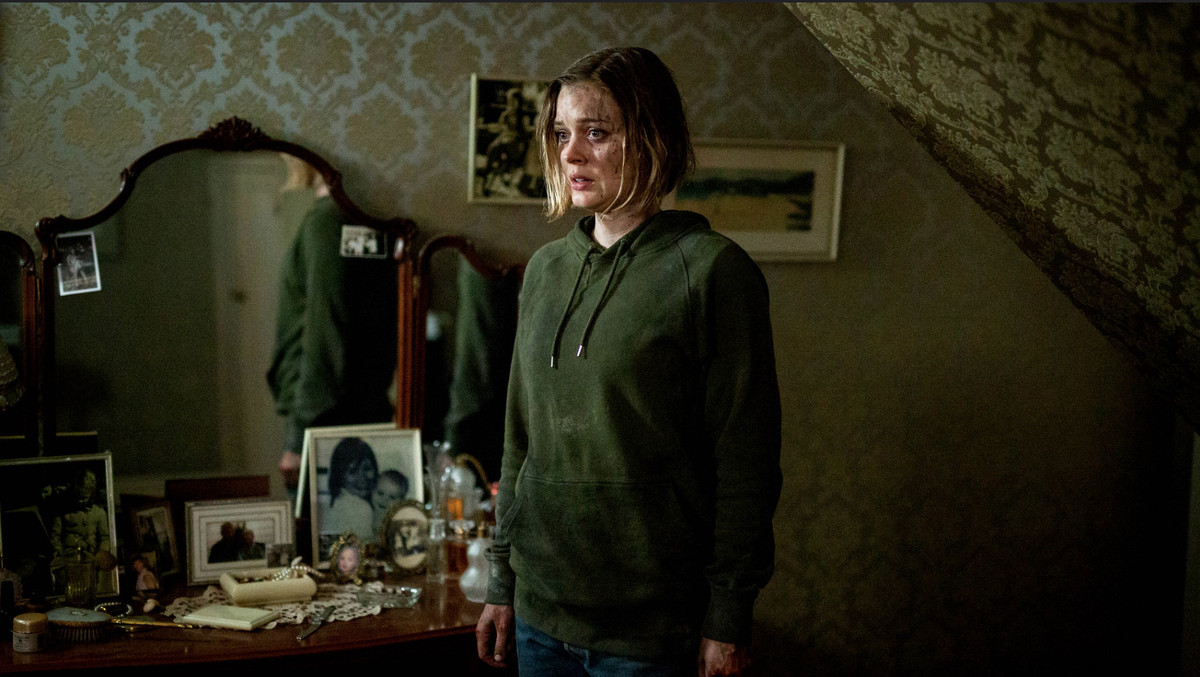 Bella Heathcote, spattered with blood and wearing a green hoodie, stars offscreen at something unnerving while standing in front of a dresser covered with photos and knickknacks in Relic.