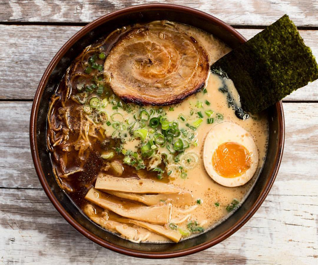 A bowl of light brown broth with a halved boiled egg, a sheet of seaweed, a pile of green sliced green onions, darker brown sauce, and a sliced meat, and vegetables.