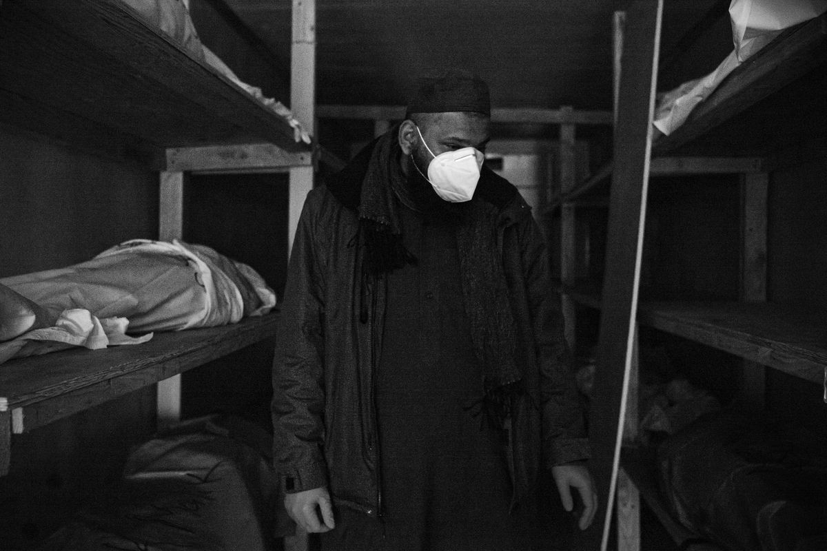 Funeral homes and hospitals have found it impossible to keep up with the number of bodies amid the virus. In this picture, Imam Ahmed Ali walks through a refrigerated truck in front of a funeral home.