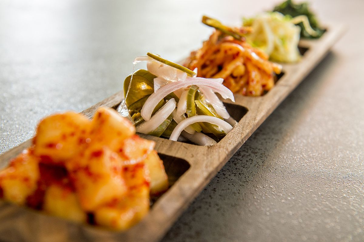 The banchan tray with five seasonal side dishes including kimchi with daikon radish, pickled jalapenos and onions, Korean kimchi, bean sprouts, and kale with sesame seeds.