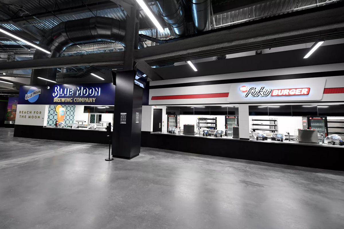 An empty concourse with a beer bar and a burger stand