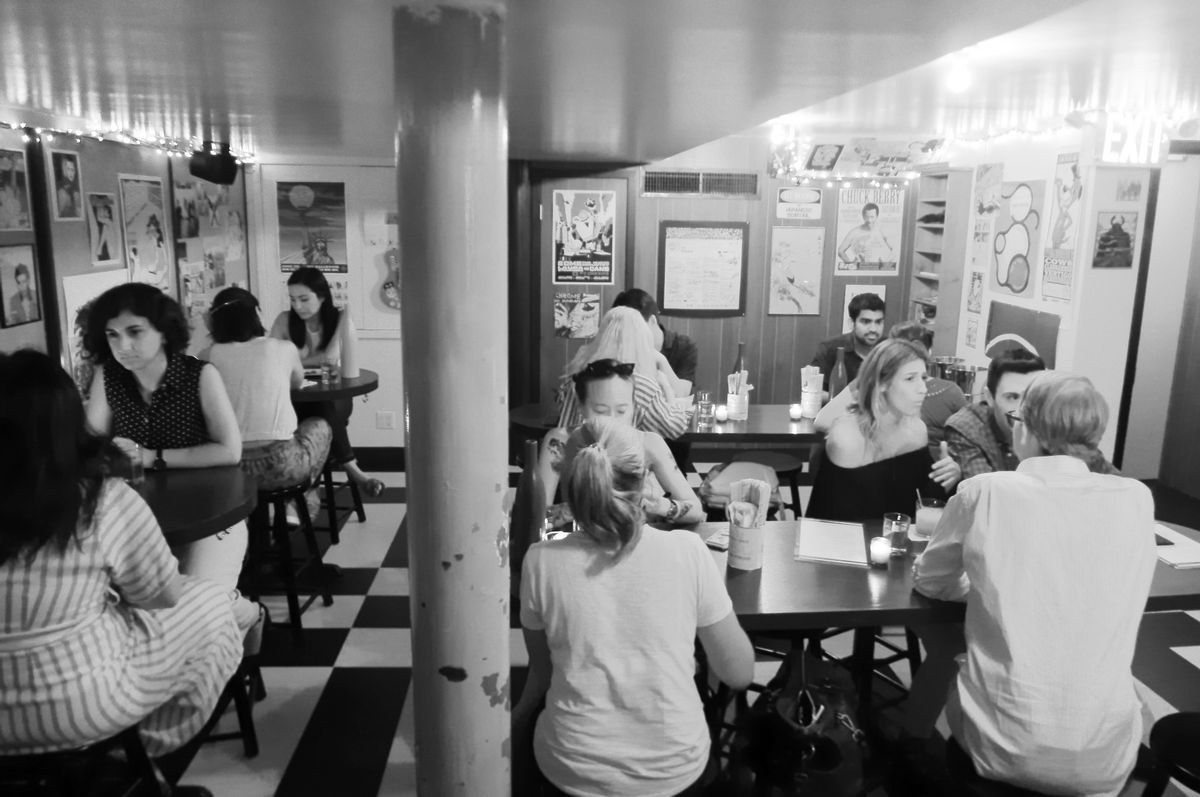 A black and white photo of a basement dining room with people sitting at high tables here and there...