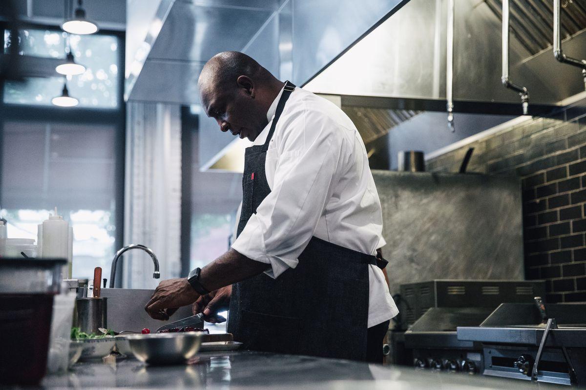 Chef Erick Williams preparing a dish at Virtue Restaurant and Bar.