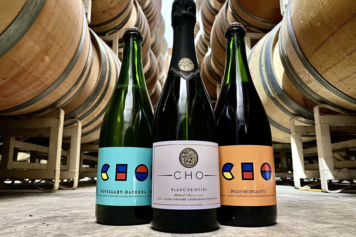"""Three bottles of wine sit on the ground of a cellar, with barrels looming in the background. They all say """"Cho"""" on the label"""