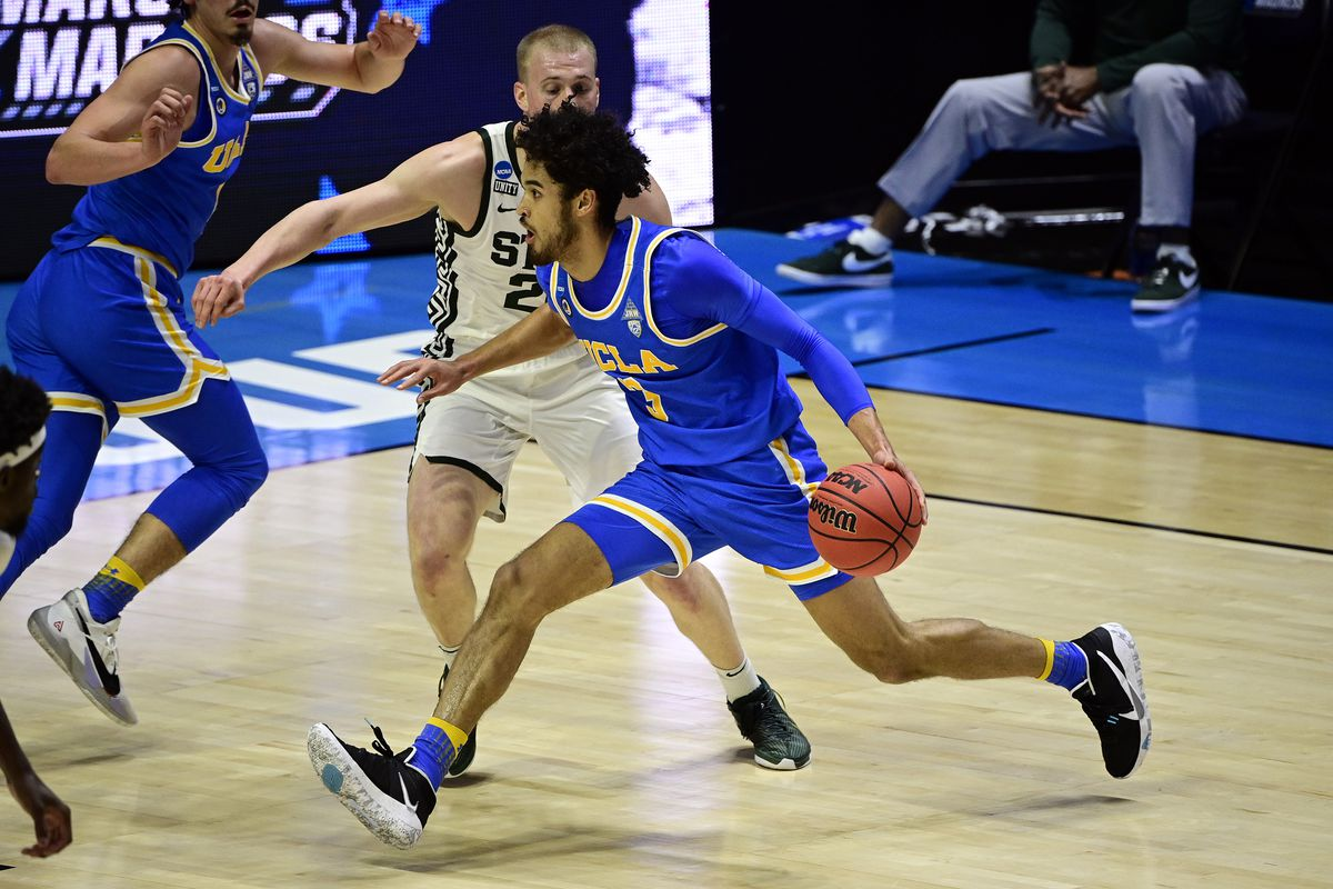 UCLA Bruins guard Johnny Juzang drives against Michigan State Spartans forward Joey Hauser in the first half during the First Four of the 2021 NCAA Tournament at Mackey Arena.
