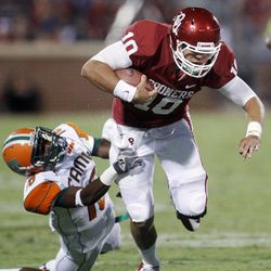 """FILE - In this Sept. 8, 2012, file photo, Oklahoma quarterback Blake Bell (10) is tackled by Florida A&M defender Antwain Mathews (16) during the fourth quarter of an NCAA college football game in Norman, Okla. When Oklahoma coach Bob Stoops ran into Kansas State quarterback Collin Klein at Big 12 media days this summer, he had an admission to make. The Sooners had stolen pages out of the Wildcats' playbook in creating the """"Belldozer"""" short-yardage package featuring backup quarterback Blake Bell."""