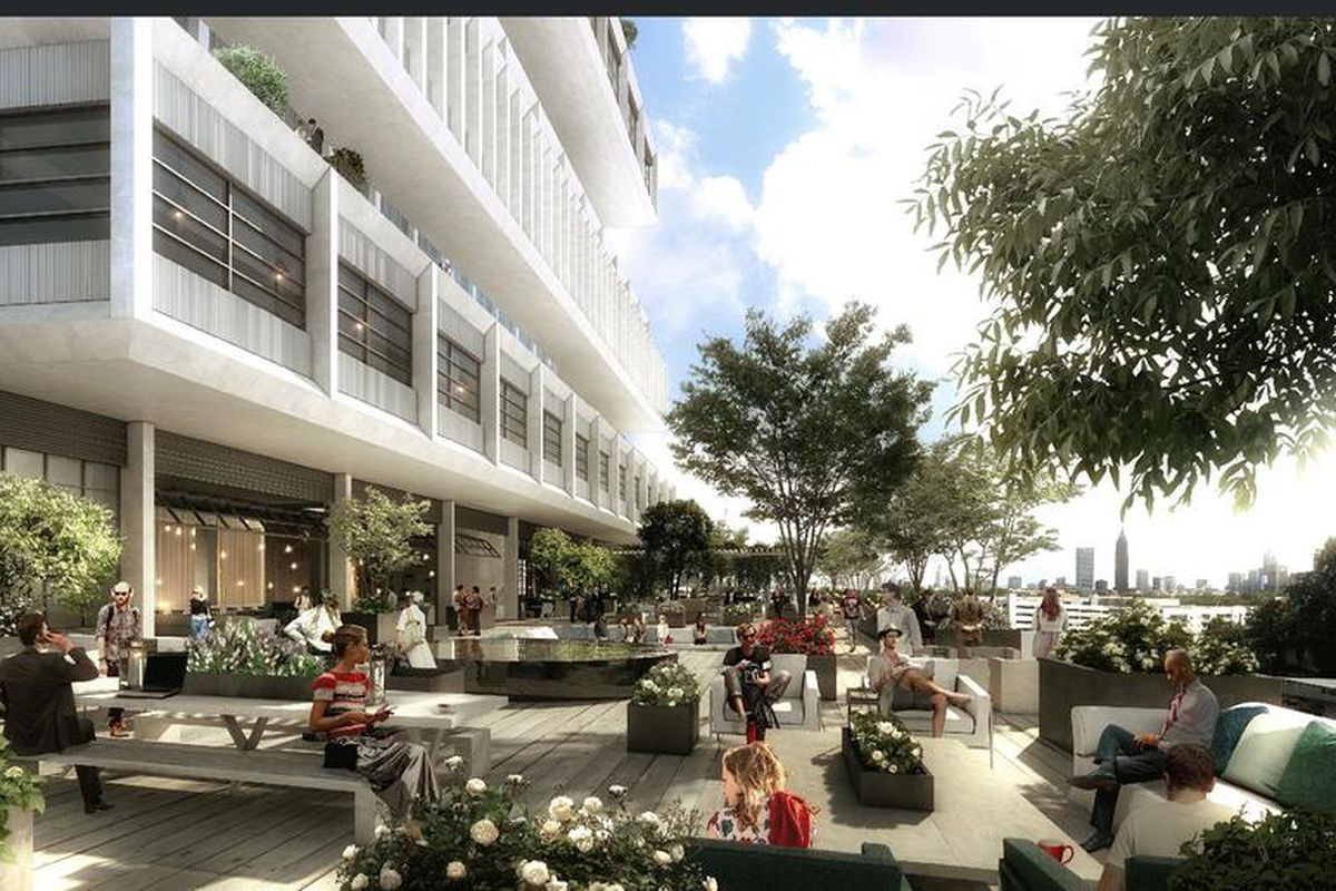 A large tree-filled terrace with people, shaded by a  white industrial-looking office building with offset floors and large balconies.