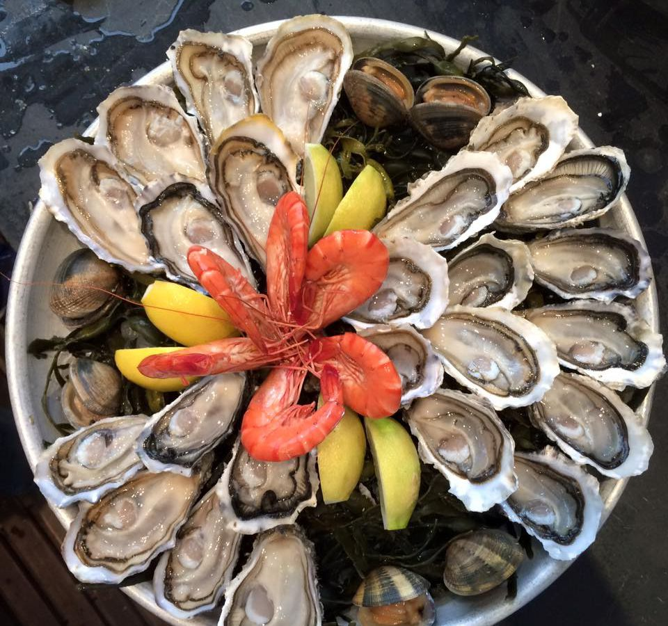 From above, a large dish of shucked oysters, with bright shrimp and lemon wedges in the center