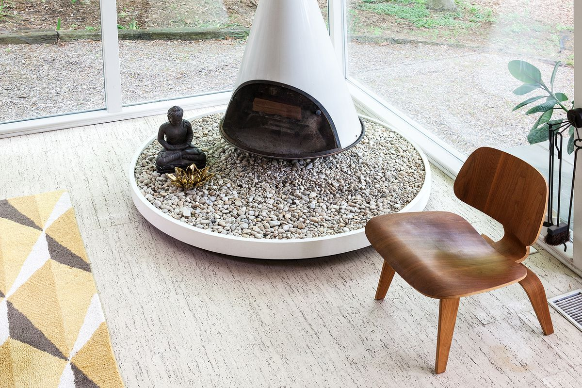 A white, metal, conical fireplace sits on a bed of gravel. This is original to the house. The white travertine floor with a strong pattern is also original.