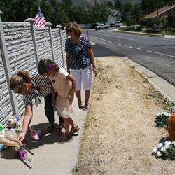 Toni Linsenmeyer, her daughter, Ava, 5, and her mother, Noemi Simons, left to right, place flowers at a memorial to the victims of Tuesday's fatal shooting on Alta Canyon Drive in Sandy on Wednesday, June 7, 2017. Ava Linsenmeyer was in a kindergarten class with Jase Rackley, who was killed in the shooting.