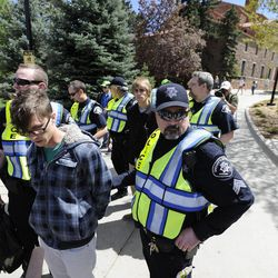 University of Colorado senior Jonathan Edwards, front, and senior John Demopoulos, middle, are arrested by Boulder County Sheriff deputies for trespassing on Norlin Quad by going past the police tape on the University of Colorado campus in Boulder, Colo., on Friday, April 20, 2012. A block-long line of protesters marched onto the University of Colorado, testing the school's determination to push the annual April 20 marijuana celebration off campus.