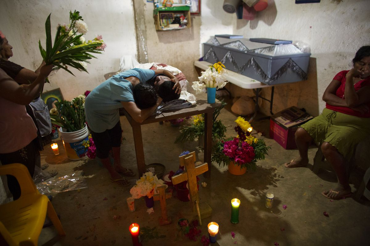 """February 8: Maribel Julio Meneses weeps over the body of her son Daniel Julio Julio, a """"community police"""" vigilante in the village of Huamuchapa, near Tecoanapa, Guerrero state, Mexico. The 22-year-old vigilante was ambushed and killed while on duty. Read"""