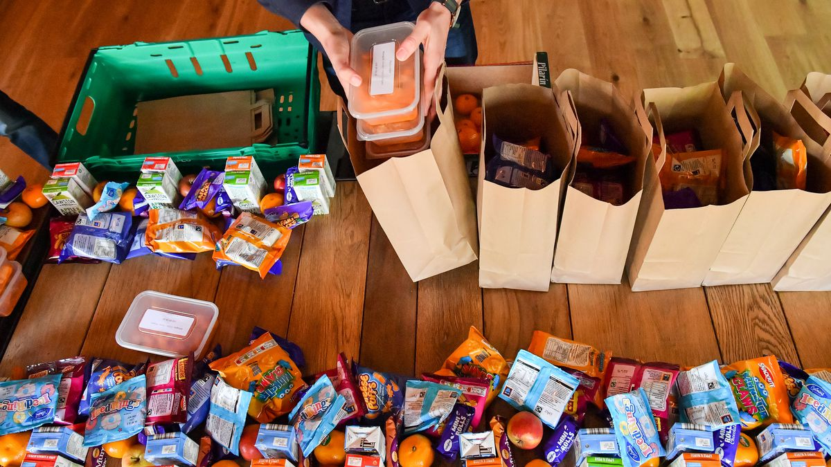 Man packs two plastic containers full of food into a brown paper bag, with other assorted food items also on the table.