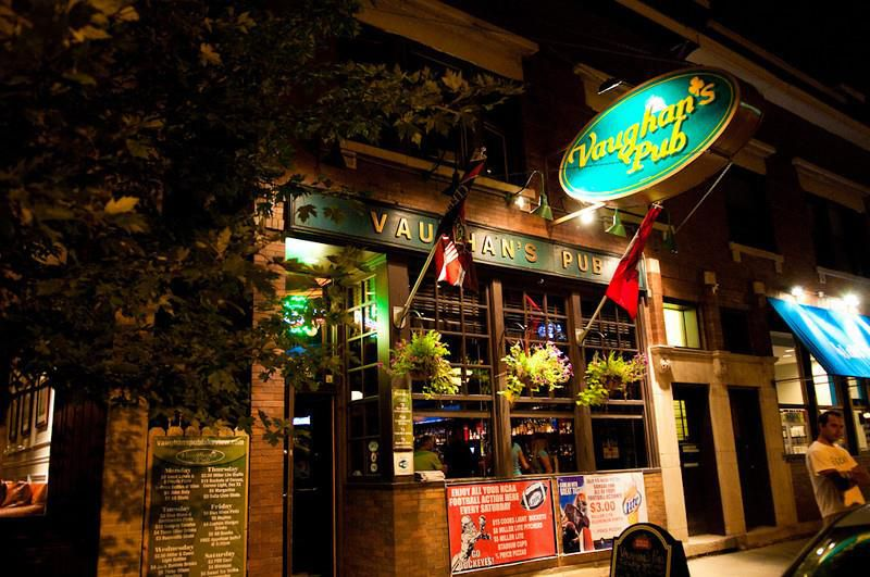 """The outside of a brick pub at night. A large green hanging sign reads """"Vaughan's Pub."""" Large flags hang outside."""