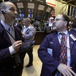 Specialist Douglas Johnson, right, works at his post on the floor of the New York Stock Exchange, Monday, April 16, 2012, in New York. The Dow Jones industrial average rose but other stock indexes fell early Monday as a strong report on retail sales didn't dispel worries about the economy.