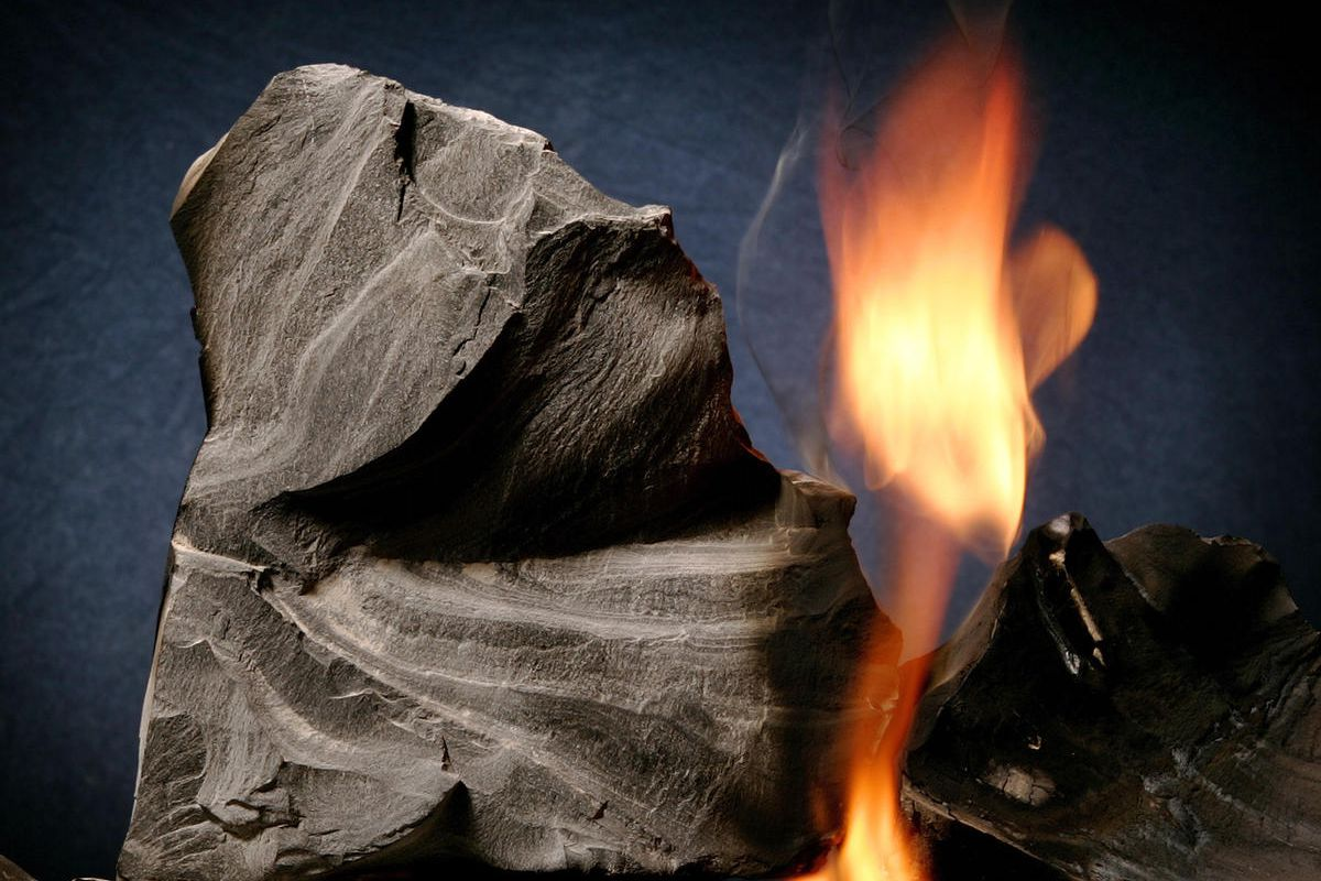 FILE - Oil shale rock burns on its own once lit with a blow torch Monday, Aug. 15, 2005, in Sandy, Utah.