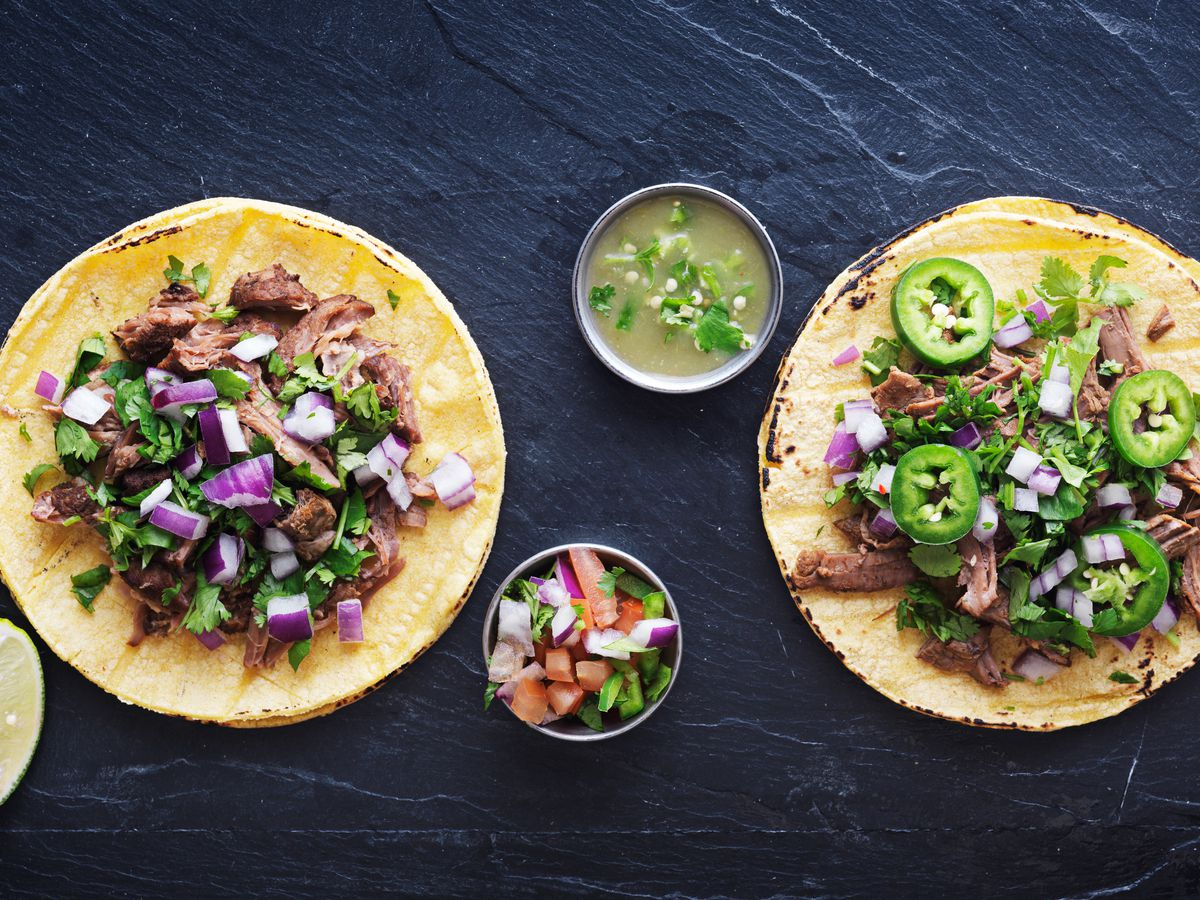 An overhead photo of two tacos piled high with chopped onions, cilantro, and jalapenos, accompanied by slices of lime.