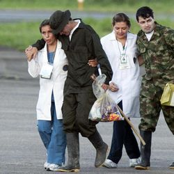 FILE - In this April 2, 2012 file photo, accompanied by medical personnel, former hostage army Sgt. Luis Alfonso Beltran, right, arrives to an airport after being released by the Revolutionary Armed Forces of Colombia (FARC) in Villavicencio, Colombia. Second from left is an unidentified freed hostage. Many former hostages say they have found it impossible to successfully resume the lives they lived before captivity, and doctors and psychologists interviewed by The Associated Press said the emotional wounds of some may never heal.