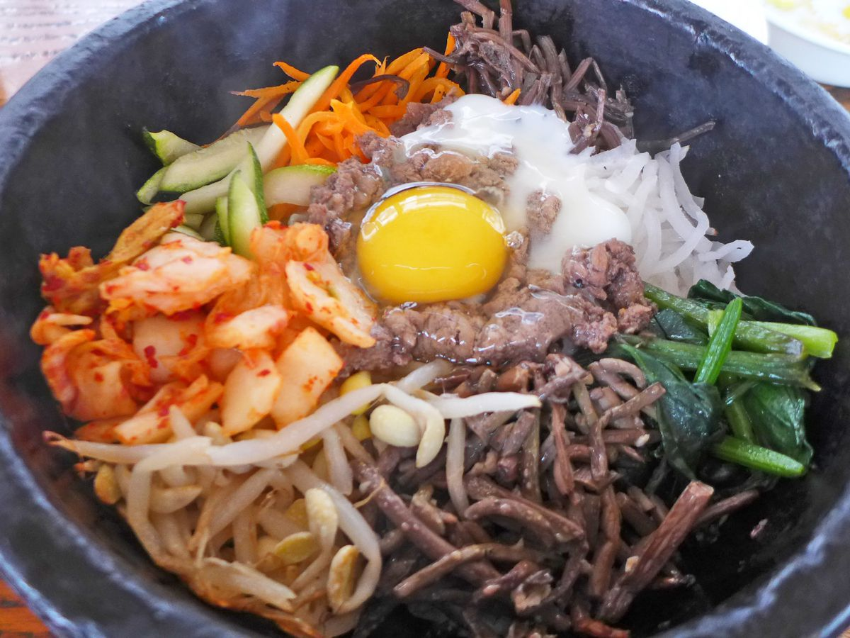 A black stone bowl with various ingredients topped with a raw egg.