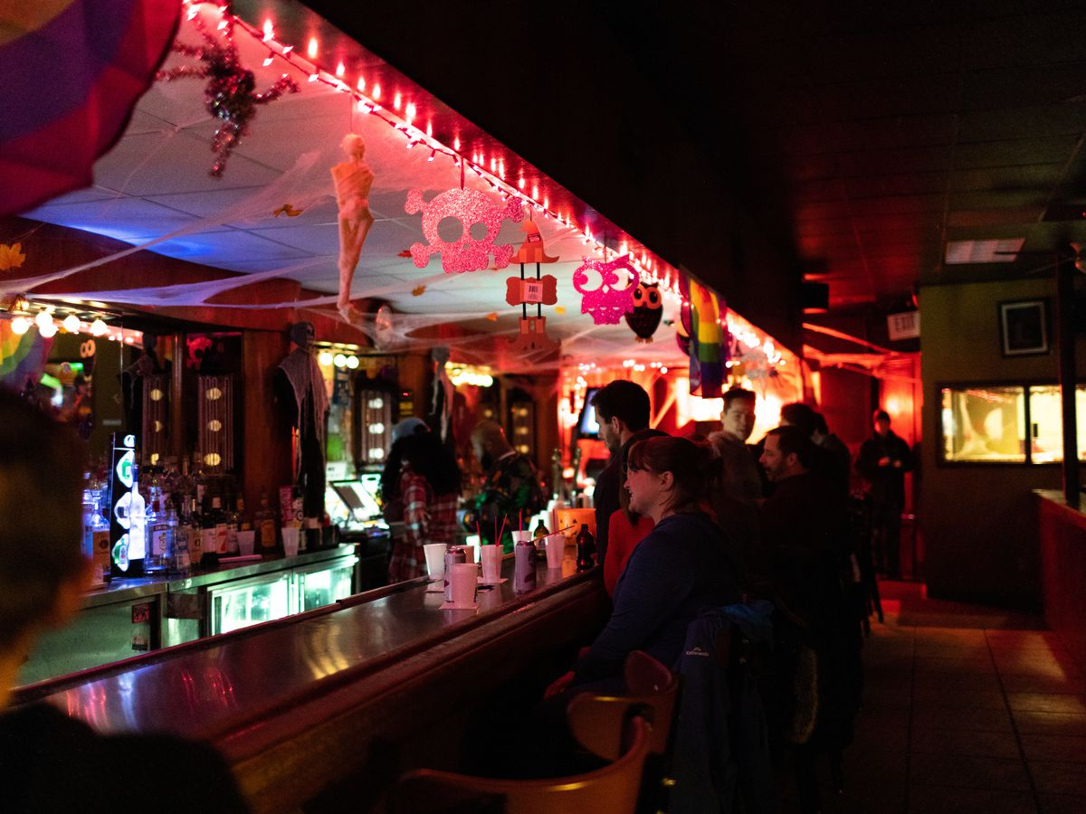 People sit at the Temple Bar beneath bright red lights and Halloween decorations.