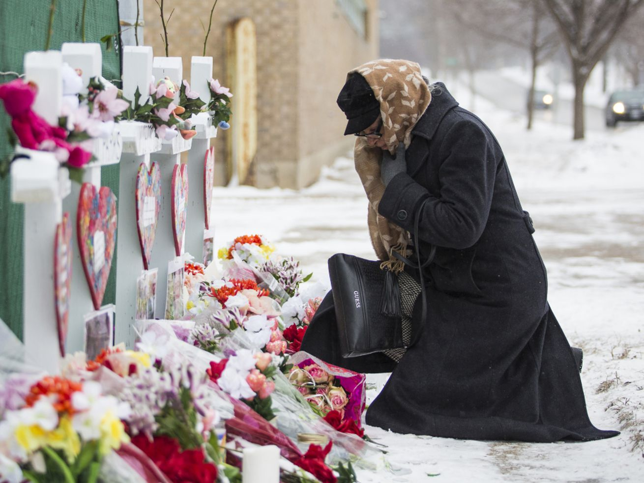 A mourner pays respects at a memorial for the five people killed in a shooting at the Henry Pratt Company in Aurora in February.