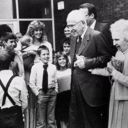 LDS Church President Ezra Taft Benson and his wife, Flora Benson, greet a group of children, circa 1986.