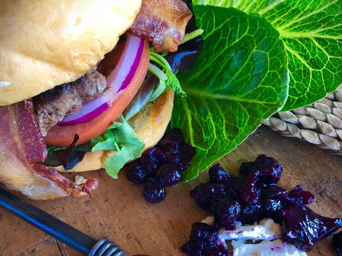 Hamburger on a bed of collard greens on a wood board with an iron implement, goat cheese, and blueberry sauce.