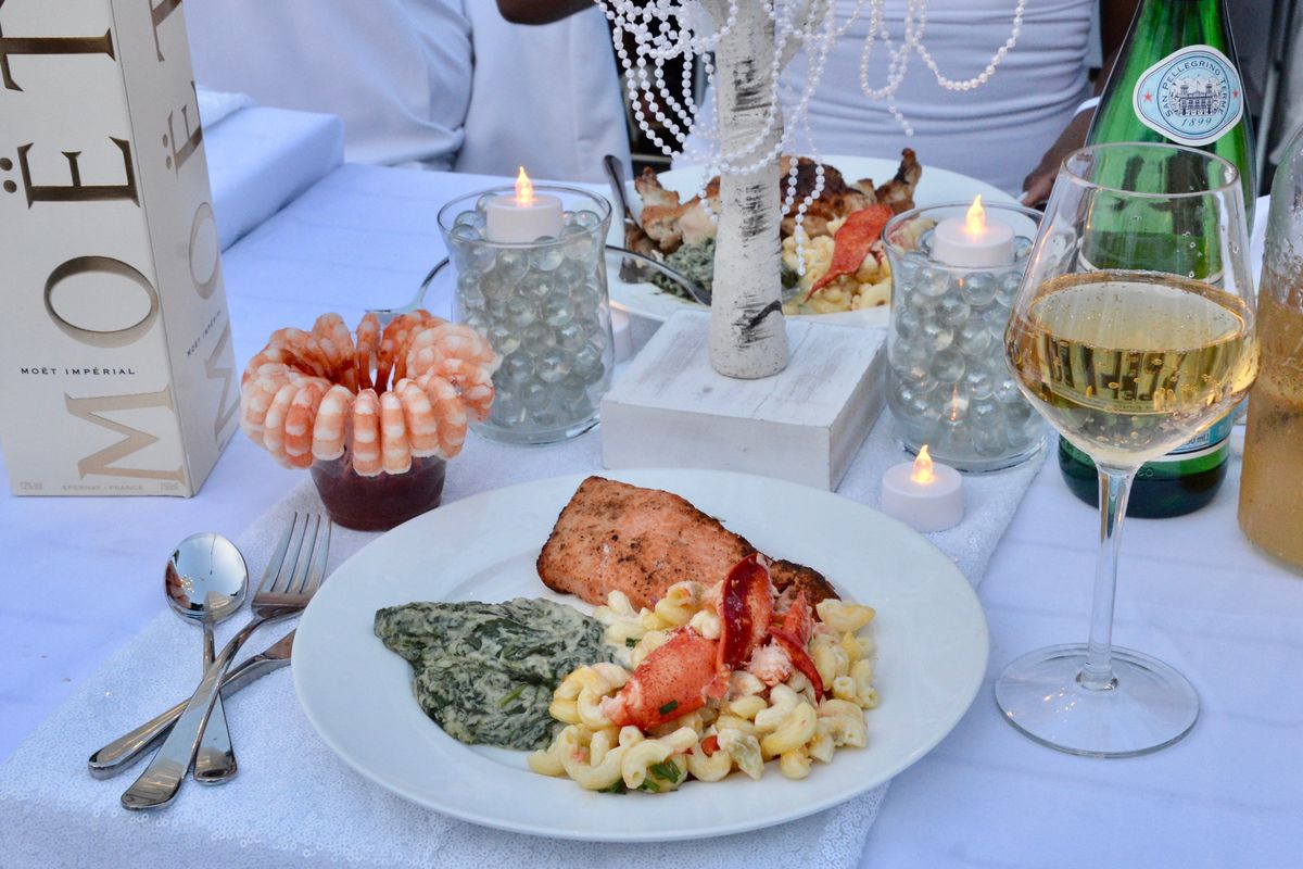 plate of food, shrimp cocktails, glass of wine, and lit candles