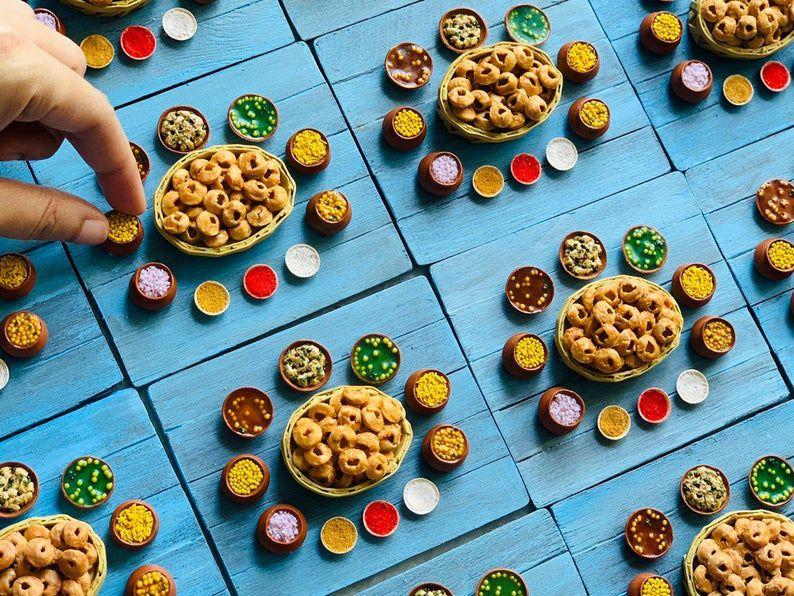 Quatro miniaturas de pani puri e uma mão para a escala
