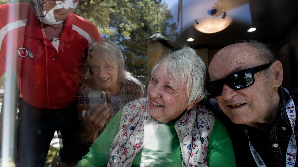 """George and Nita Lutes visit with their nephew and his wife, Tim and Cathy Chambless, through glass in April 2020. A proposed federal """"Essential Caregivers Act"""" would let facility residents name caregivers who could not be barred from visiting in a public health emergency. HR 3733 has bipartisan sponsorship. The Lutes died in December."""