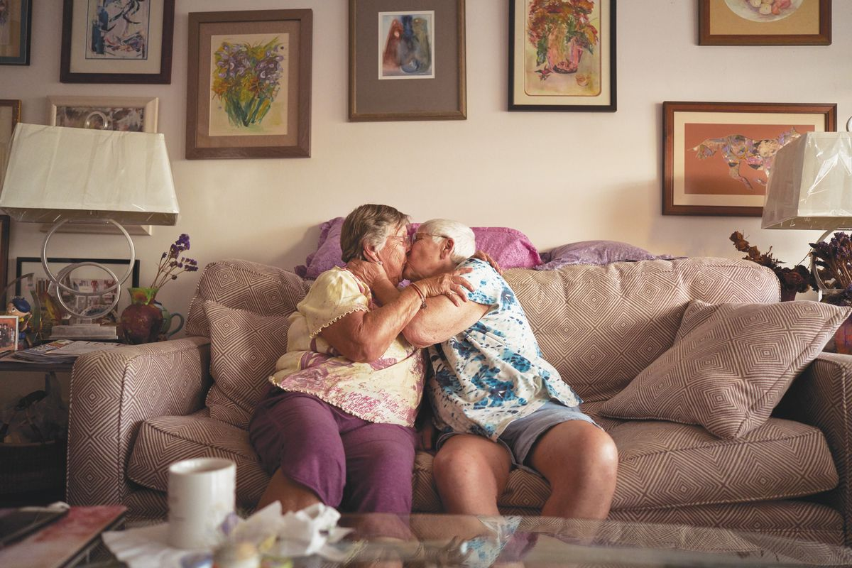Two older women kiss while holding each other and sitting on a beige couch. Framed artworks cover the off-white walls.