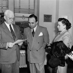 """Flanked by his wife and a U.S. Marshall (the couple was charged with tax evasion) in 1951. Photo via the <a href=""""http://bigstory.ap.org/content/james-j-boyle-mickey-cohen-lavonne-cohen"""">AP</a>."""