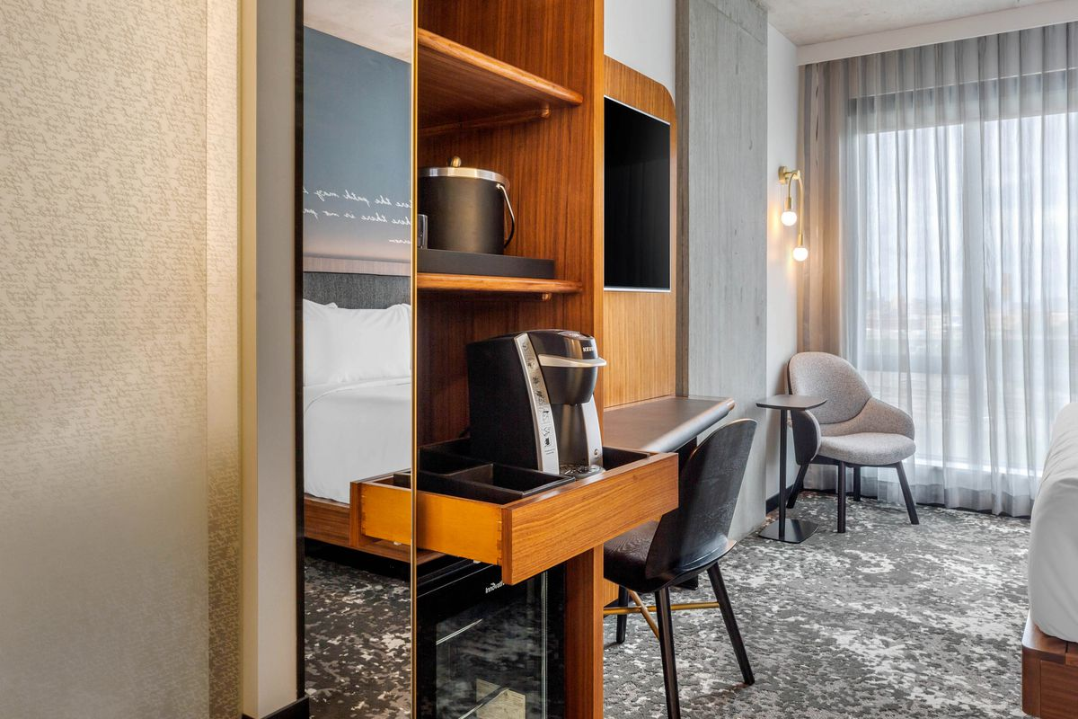 A hotel room with a desk and other furniture, and a coffee maker displayed prominently.
