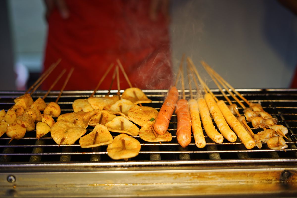 skewers sit on a grill.