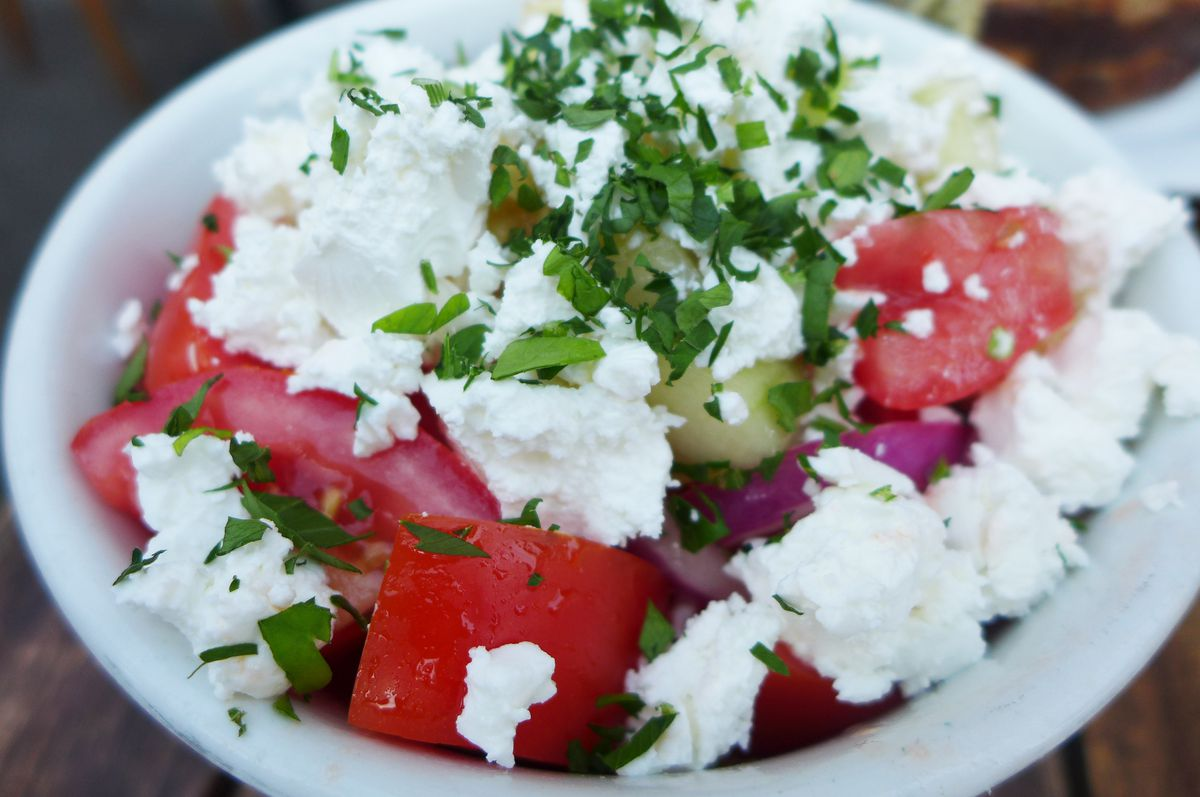 A bowl of tomatoes, cucumbers, and fluffy white ricotta.