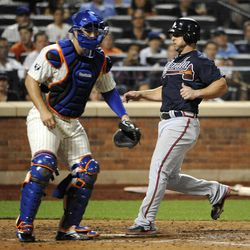 Atlanta Braves' Dan Uggla scores at home plate on a sacrifice fly by David Ross as New York Mets catcher Kelly Shoppach waits for the throw in the seventh inning of a baseball game on Friday, Sept. 7, 2012, at Citi Field in New York.