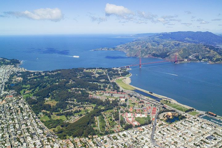 An aerial view of San Francisco. There are city buildings, a body of water, and a red bridge spanning the water.