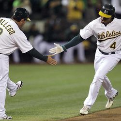 Oakland Athletics' Coco Crisp, right, is congratulated by third base coach Mike Gallego after Crisp hit a home run off Seattle Mariners' Blake Beavan during the first inning of a baseball game Friday, Sept. 28, 2012, in Oakland, Calif.