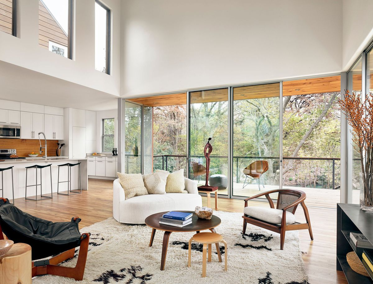Living room with big windows and modern furniture.
