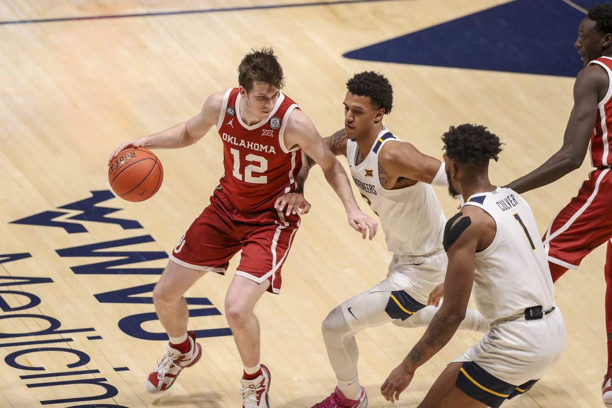 Oklahoma Sooners guard Austin Reaves dribbles against West Virginia Mountaineers forward Jalen Bridges during the second half at WVU Coliseum.