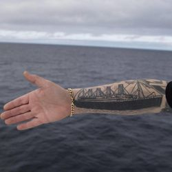 Derek Chambers from Belfast shows his tattoo of the Titanic, aboard the MS Balmoral Titanic memorial cruise ship in the Atlantic Ocean, Thursday, April 12, 2012. Nearly 100 years after the Titanic went down, the cruise with the same number of passengers aboard is setting sail to retrace the ship's voyage, including a visit to the location where it sank. The Titanic Memorial Cruise departed Sunday, April 8, from Southampton, England, where the Titanic left on its maiden voyage and the 12-night cruise will commemorate the 100th anniversary of the sinking of the White Star liner. With 1,309 passengers aboard, the MS Balmoral will follow the same route as the Titanic and organizers are trying to recreate the onboard experience minus the disaster from the food to a band playing music from that era.