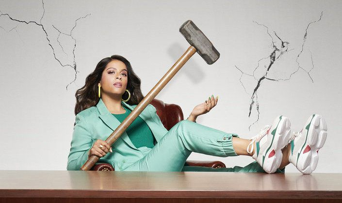 lilly singh wields a hammer as she puts her feet up on a desk in a promo shot for her new late night show