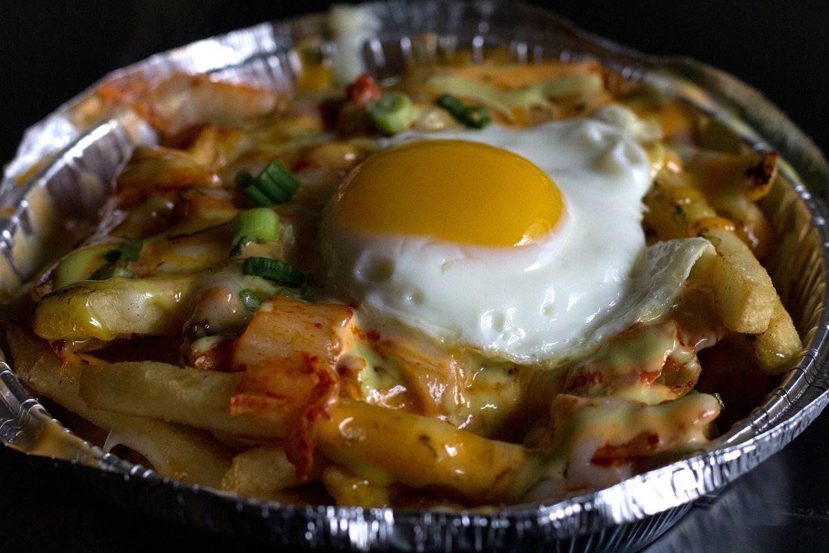 A takeout container filled with french fries, which are topped with cheese, kimchi, and a fried egg