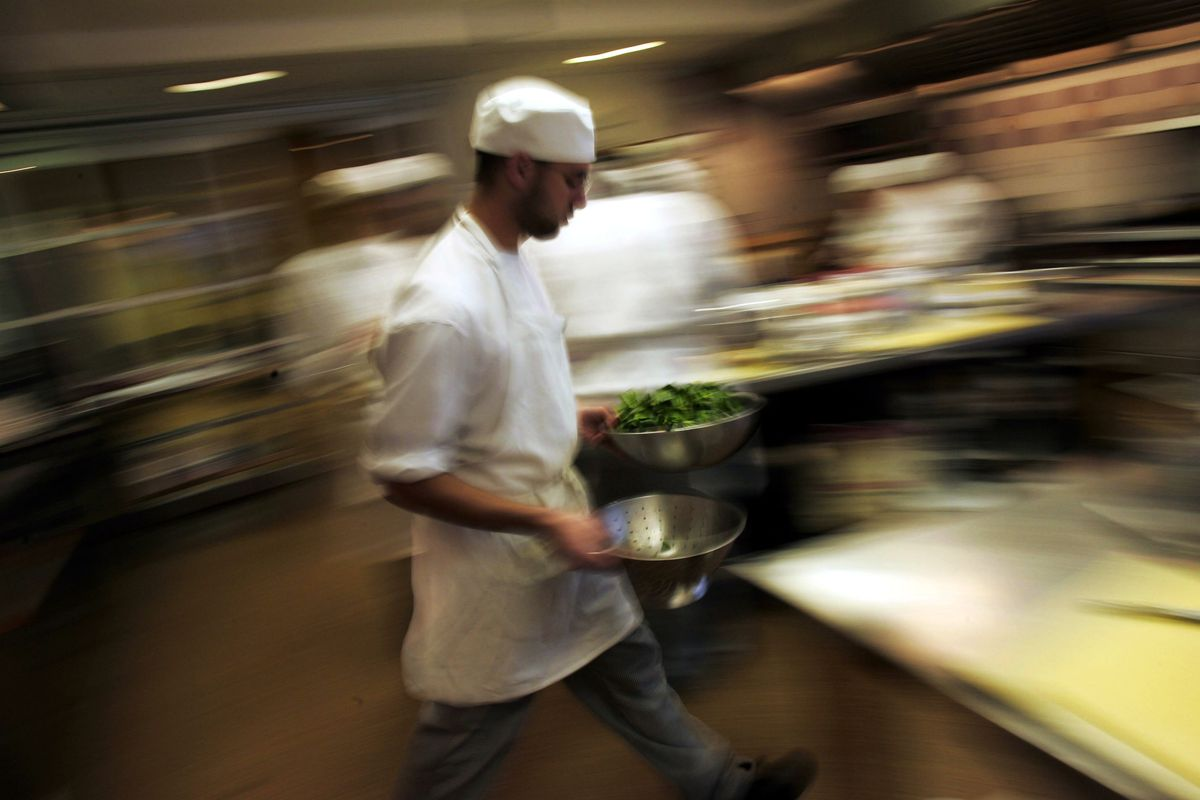 A man in chef's whites rushes through the kitchen with greens