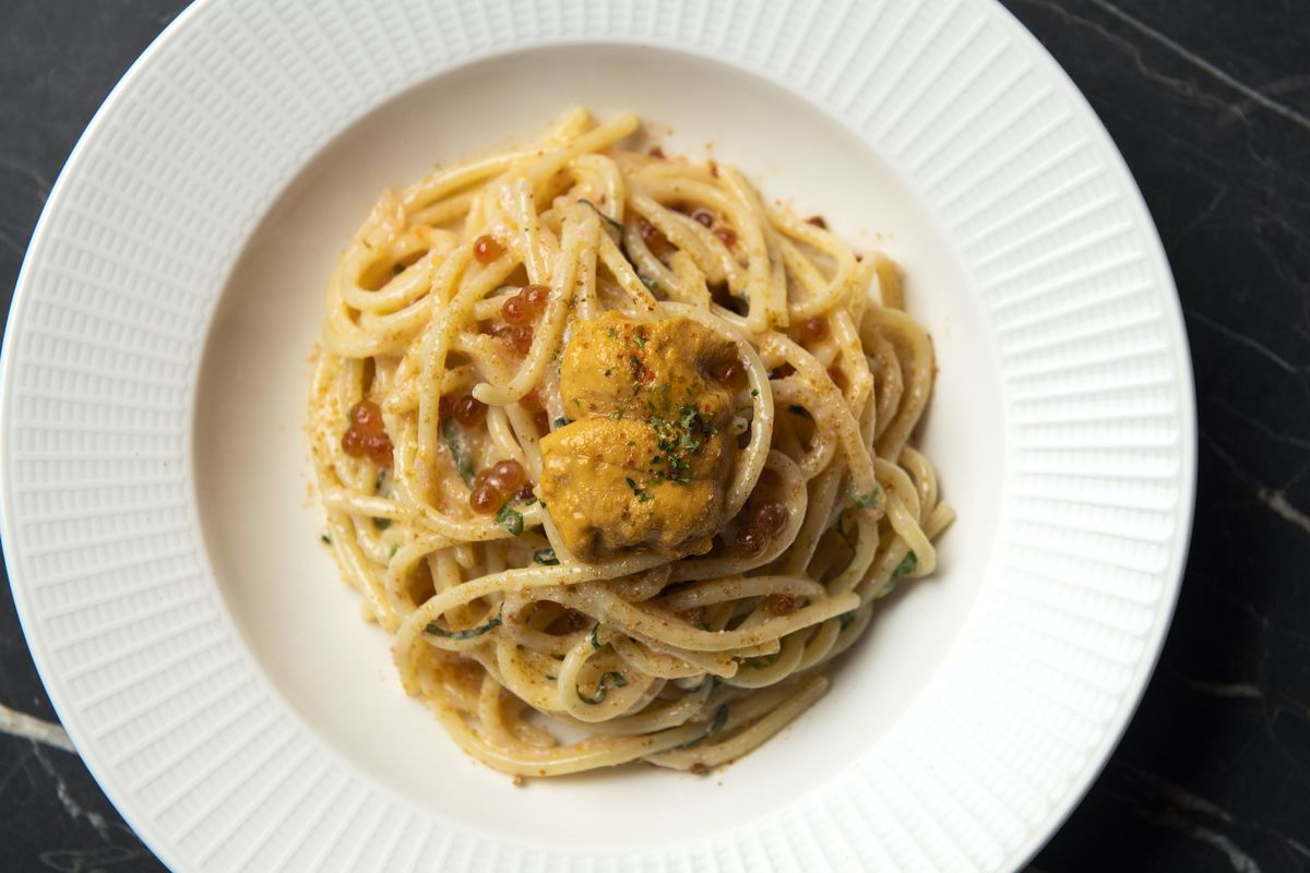 An aerial photo of a white plate with yellow pasta topped with four kinds of roe